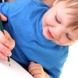 O menino pequeno quer desenhar. foto de stock