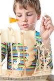 O menino pequeno trabalha com zelo no navio artificial Foto de Stock Royalty Free
