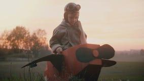 O menino piloto pequeno feliz obtém no plano do cartão do divertimento, levanta-se no campo do outono do por do sol que joga e qu filme