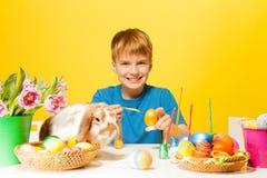 O menino pinta ovos da páscoa com coelho bonito na tabela Imagem de Stock