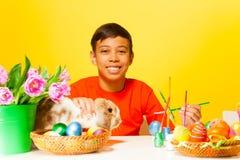 O menino pinta ovos da páscoa com coelho na tabela Fotografia de Stock
