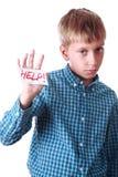 O menino pobre bonito em uma camisa azul mostra uma ajuda da mensagem! Fotografia de Stock
