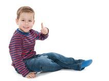 O menino pré-escolar no assoalho mantém seu polegar Imagem de Stock