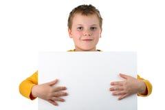 O menino prende o quadro de avisos em branco com o isolado inteiro das mãos Fotografia de Stock Royalty Free