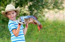 O menino prende peixes grandes Foto de Stock