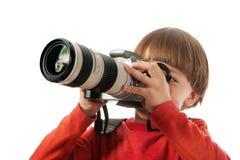 O menino prende uma câmera foto de stock