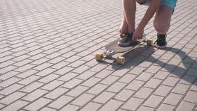O menino prepara-se para montar o skate vídeos de arquivo