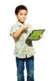 O menino preto mostra a foto no computador da tabuleta imagem de stock