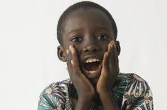 O menino preto pequeno surpreendido e entusiasmado com branco isolou o backg imagens de stock royalty free