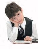 O menino, a pupila da escola tem o controle sobre o livro de texto Fotos de Stock Royalty Free