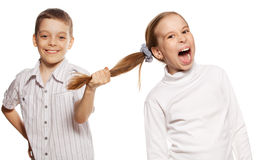 O menino puxa o cabelo da menina Fotografia de Stock