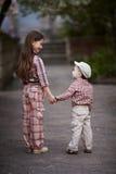 O menino que abraça a irmã bonito e olha acima Fotografia de Stock