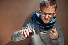 O menino que 10 anos eram doentes ele não quis beber o xarope amargo Foto de Stock