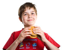 O menino que come um Hamburger. Foto de Stock Royalty Free