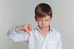 O menino que dá os polegares assina para baixo Foto de Stock