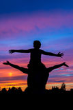 O menino que está no pai empurra a silhueta com por do sol colorido Fotografia de Stock