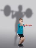 O menino que faz a ocupa exercita com a silhueta do weightlifter atrás dele Fotos de Stock Royalty Free