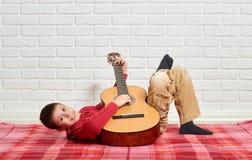 O menino que joga a música na guitarra, vestida em uma camiseta de lã vermelha, encontra-se em uma cobertura quadriculado vermelh fotografia de stock royalty free