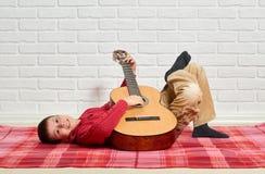 O menino que joga a música na guitarra, vestida em uma camiseta de lã vermelha, encontra-se em uma cobertura quadriculado vermelh imagens de stock
