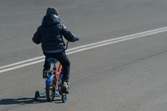 O menino que monta uma bicicleta para trás vê em uma estrada de passeio Fotografia de Stock Royalty Free