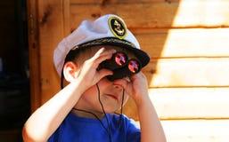O menino que olha com o binocular Imagens de Stock