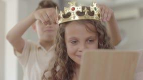 O menino que põe a coroa sobre a cabeça da menina encaracolado que olha no espelho A coroa é demasiado grande para a criança, cri video estoque