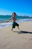 O menino que salta ao redor na praia Fotografia de Stock