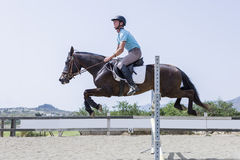 O menino que salta com cavalo Imagens de Stock Royalty Free