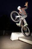 O menino que salta com sua bicicleta sobre uma rampa fotos de stock