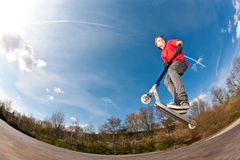 O menino que salta com um 'trotinette' Fotos de Stock Royalty Free