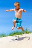 O menino que salta de uma duna de areia Fotos de Stock