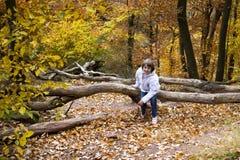 O menino que salta e que joga com as folhas de outono douradas Imagem de Stock