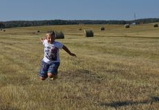 O menino que salta em monte de feno próximos Fotografia de Stock