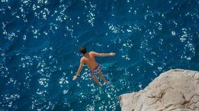 O menino que salta fora da rocha no Mar Egeu Foto de Stock Royalty Free