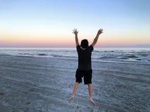 O menino que salta na praia Imagem de Stock