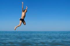 O menino que salta no mar fotos de stock royalty free