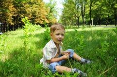 O menino que senta-se na grama Imagem de Stock Royalty Free
