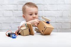 O menino que senta-se na tabela e recolhe o robô Foto de Stock Royalty Free