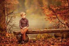 O menino que senta-se no banco fotos de stock royalty free
