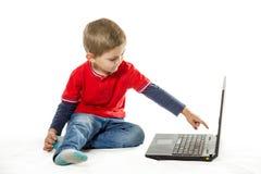 O menino que usa o portátil Imagem de Stock