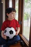 O menino quer jogar o futebol em um dia chuvoso Fotografia de Stock Royalty Free