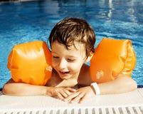 O menino real bonito pequeno no fim da piscina que sorri acima, estilo de vida vacations conceito dos povos Fotografia de Stock