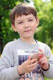 O menino realiza em sua mão um ovo de chocolate foto de stock royalty free
