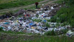 O menino recolhe o lixo no lixo vídeos de arquivo