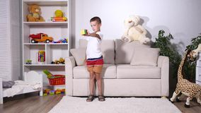 O menino recolhe um cubo do rubik e dos pontos à câmera vídeos de arquivo