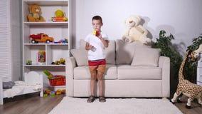 O menino recolhe um cubo do rubik e dos pontos à câmera video estoque