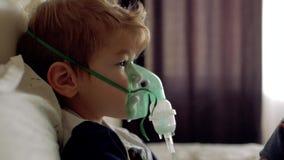 O menino respira através da máscara transparente do inalador O menino ele mesmo faz Máscara da inalação na cara da pancadinha filme