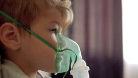 O menino respira através da máscara transparente do inalador O menino ele mesmo faz inalações Máscara da inalação na cara da panc video estoque