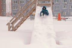 O menino rola para baixo uma corrediça de madeira nevado durante uma queda de neve imagem de stock