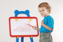 O menino sério bonito pequeno desenhou um diagrama do crescimento Foto de Stock